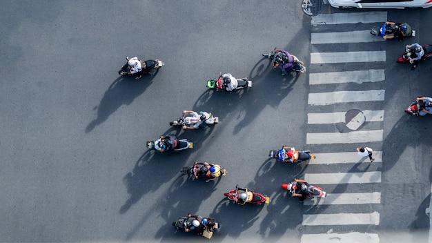 De hoogste luchtmening van onduidelijk beeldbikers berijdt de motorfietsen om voetzebrapad over te gaan op weg met signage van het verkeerspatroon op de straat. Premium Foto