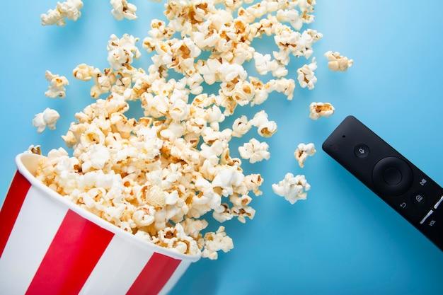 De hoogste mening van gemorste popcorn op een blauwe achtergrond met tv verwijdert Premium Foto