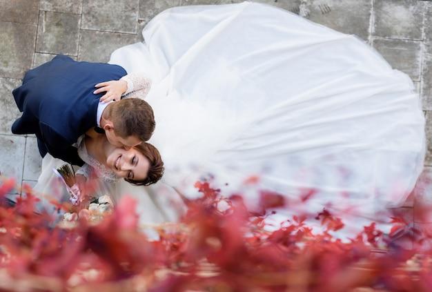 De hoogste mening van glimlachende bruid en bruidegom kust op de wang, gelukkig huwelijk Gratis Foto