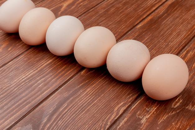 De hoogste mening van verse kippeneieren schikte lijn op een houten achtergrond Gratis Foto