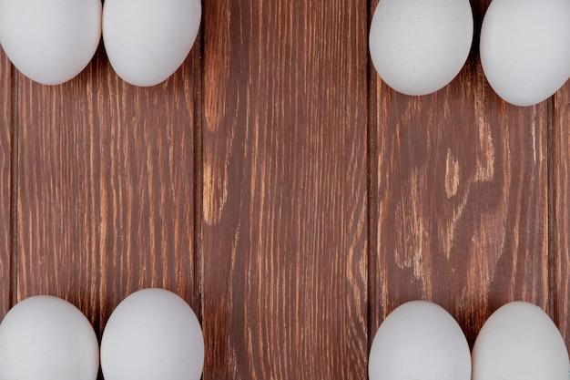 De hoogste mening van witte verse kippeneieren schikte in verschillende kanten op een houten achtergrond met exemplaarruimte Gratis Foto