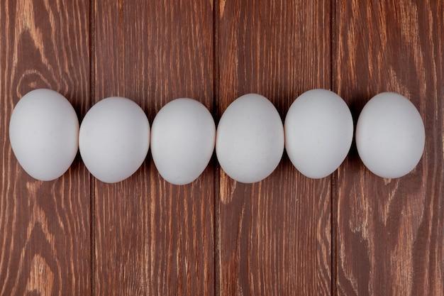 De hoogste mening van witte verse kippeneieren schikte online op een houten achtergrond Gratis Foto