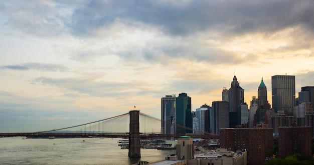 De horizon van manhattan door de brug van manhattan wordt gefotografeerd die. Premium Foto