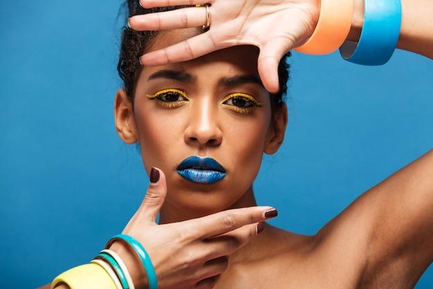 De horizontale buitensporige mulatvrouw met kleurrijke make-up en krullend haar in broodje het gesturing op camera met manier kijkt geïsoleerd, over blauwe muur Gratis Foto