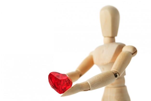 De houten figuur van een man houdt in zijn handen een rood hart op een wit oppervlak, geeft het hart Premium Foto