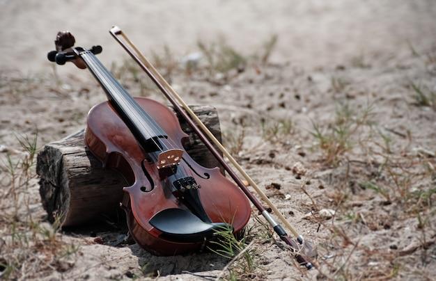 De houten viool en boog zetten naast houten raad, op het strand, onscherp licht rond Premium Foto