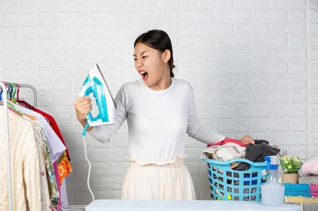 De huishoudster die boos is op zijn ijzers met een witte baksteen. Gratis Foto