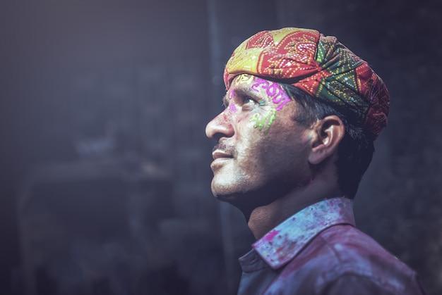 De indische mens besmeurde met kleuren op haar gezicht stelt tijdens de holi-festivalviering binnen Premium Foto