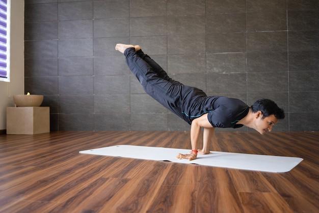 De indische yogi die de geavanceerde yoga van de handtribune doen stelt in gymnastiek Gratis Foto