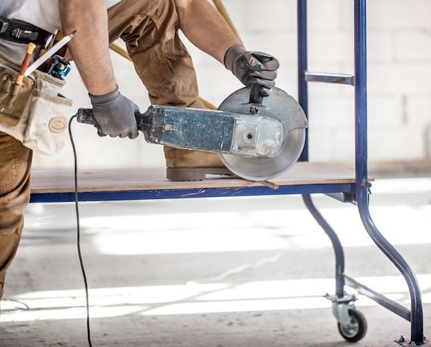 De industriële bouwer werkt met een professionele haakse slijper om stenen te snijden en binnenmuren te bouwen. elektricien. Gratis Foto