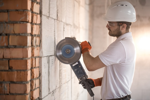 De industriële bouwer werkt met een professionele haakse slijper om stenen te snijden en binnenmuren te bouwen Gratis Foto