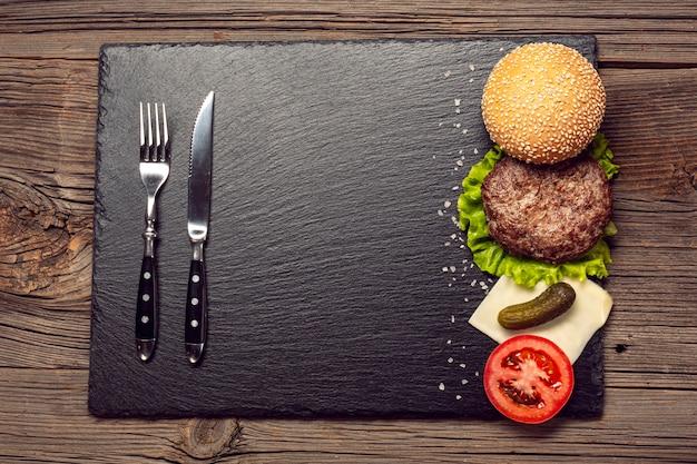 De ingrediënten van de hoogste meninghamburger op een leiraad Gratis Foto