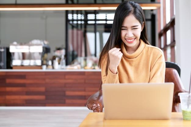 De jonge aantrekkelijke aziatische vrouwelijke student die laptop met behulp van verwerkt gegevens Premium Foto
