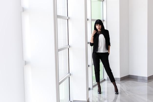 De jonge aantrekkelijke ernstige donkerbruine vrouw kleedde zich in een zwart pak die zich dichtbij het venster in bureau bevinden, die camera bekijken. Premium Foto