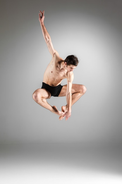 De jonge aantrekkelijke moderne balletdanser die op witte muur springt Gratis Foto
