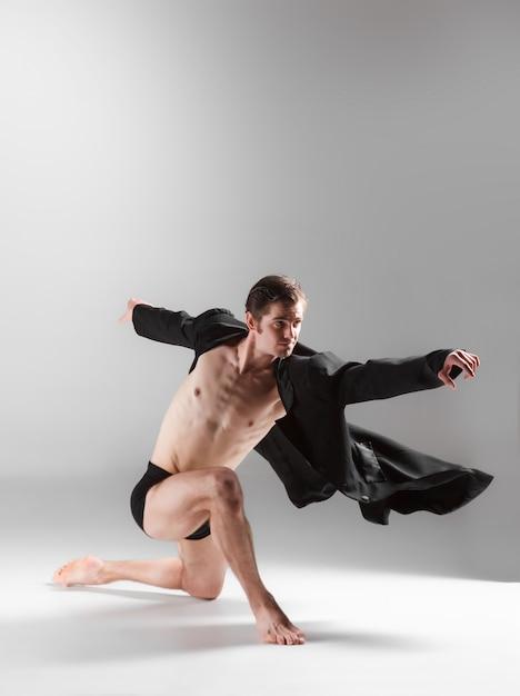 De jonge aantrekkelijke moderne balletdanser op witte muur Gratis Foto