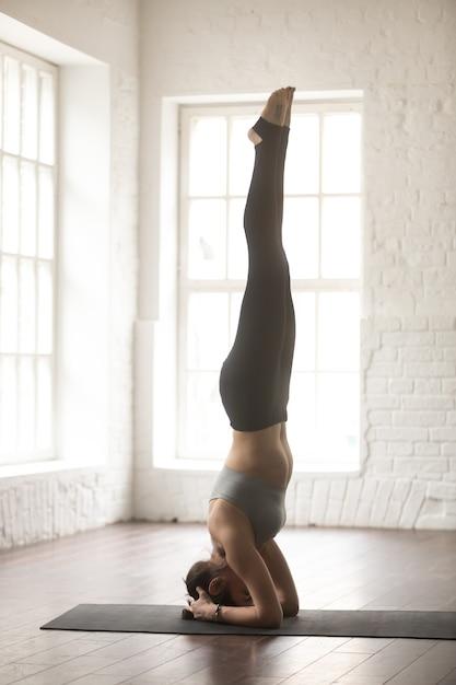 De jonge aantrekkelijke vrouw in headstand stelt, witte zolderstudio Gratis Foto