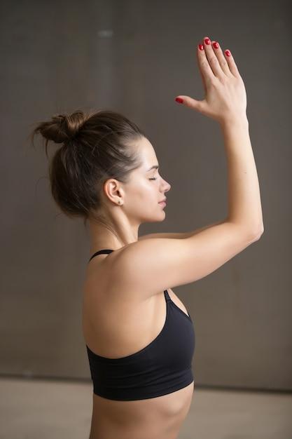 De jonge aantrekkelijke vrouw in het mediteren stelt, grijze studio backgroun Gratis Foto