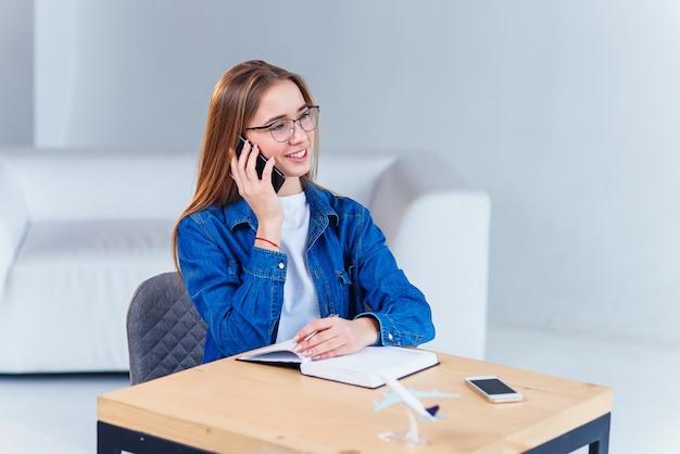 De jonge aantrekkelijke vrouwelijke student gebruikt smartphone terwijl thuis het bestuderen. Premium Foto