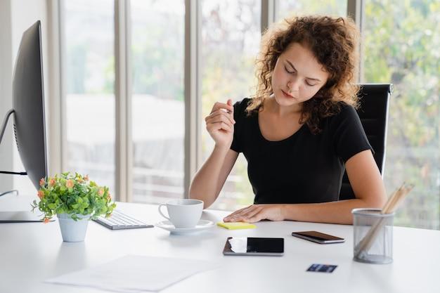 De jonge aantrekkelijke vrouwenzitting en neemt nota over zaken terwijl het werken in bureau Premium Foto