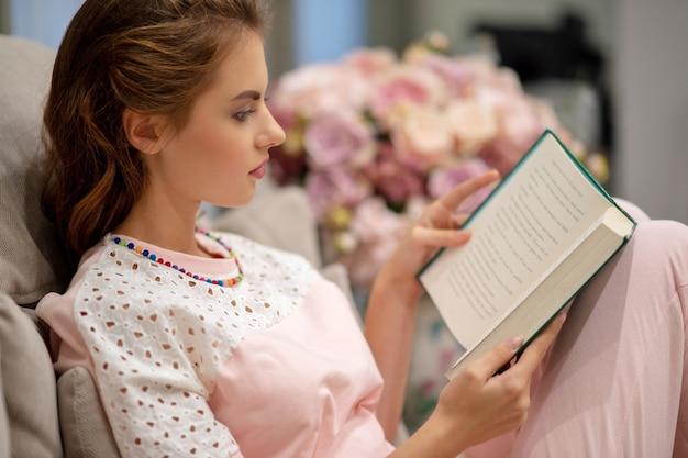 De jonge aantrekkelijke vrouwenzitting op de bank die een boek leest geniet van rust. Gratis Foto