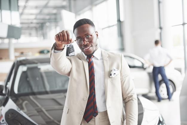 De jonge aantrekkelijke zwarte zakenman koopt een nieuwe auto, dromen komen uit. Gratis Foto