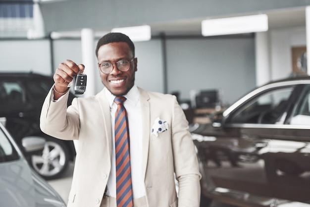 De jonge aantrekkelijke zwarte zakenman koopt een nieuwe auto, hij houdt de sleutels in zijn hand. dromen komen uit Gratis Foto