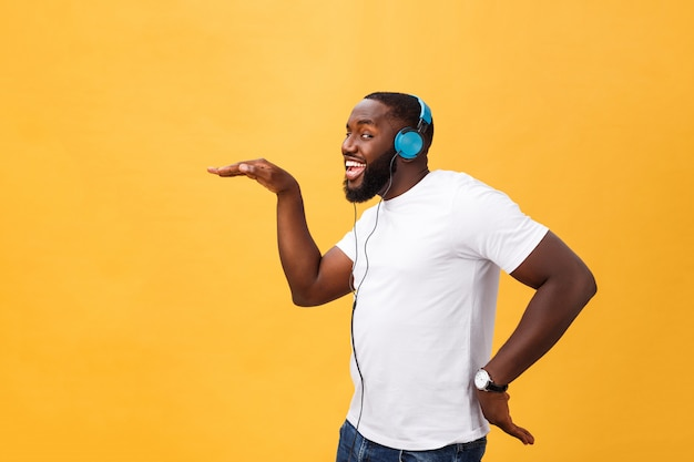 De jonge afrikaanse amerikaanse mens die hoofdtelefoon draagt en geniet van muziek die over gele gouden achtergrond dansen Premium Foto