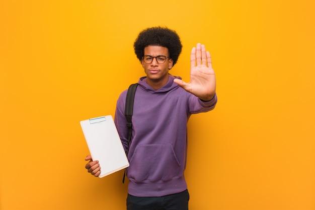De jonge afrikaanse amerikaanse studentenmens die klembord houden het zetten dient voorzijde in Premium Foto
