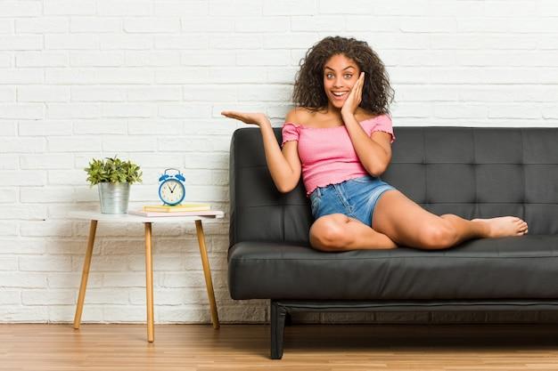 De jonge afrikaanse amerikaanse vrouwenzitting op de bank houdt exemplaarruimte op een palm, houdt wang overhandig. Premium Foto
