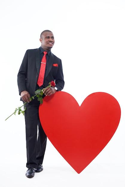 De jonge afrikaanse mens die in zwarte reeks en rode band rood houden nam toe, huidig voor valentine day Gratis Foto