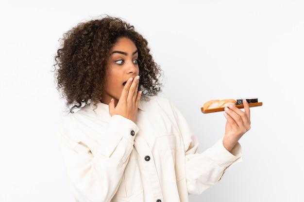 De jonge afro-amerikaanse sushi van de vrouwenholding op witte muur met verraste en geschokte gelaatsuitdrukking Premium Foto