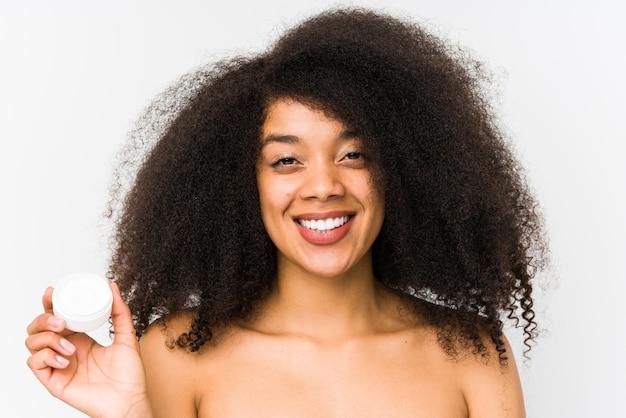 De jonge afrovrouw die een vochtinbrengende crème houden isoleerde gelukkig, glimlachend en vrolijk. Premium Foto
