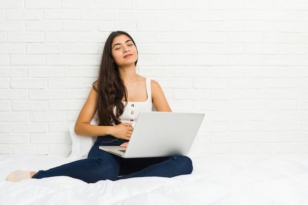 De jonge arabische vrouw die met haar laptop aan het bed werken raakt buik, glimlacht zacht, het eten en tevredenheidsconcept. Premium Foto