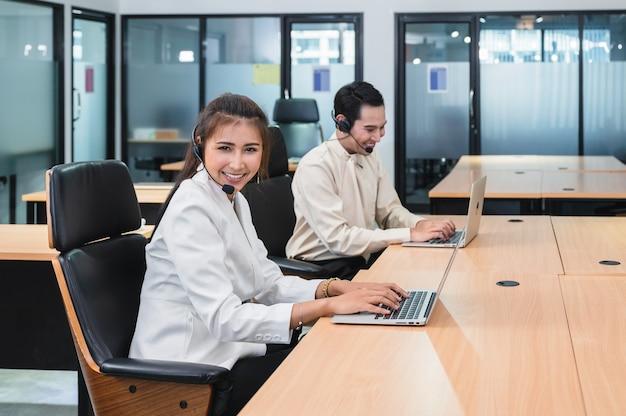 De jonge aziatische agent van de exploitantvrouw met hoofdtelefoons werkende klantenservice in call centre Premium Foto