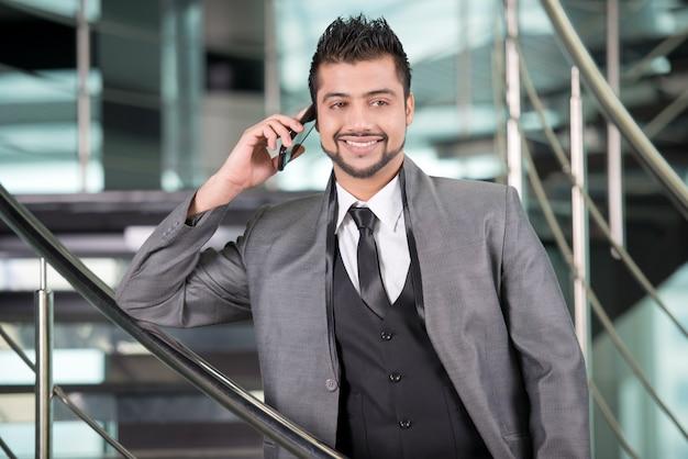 De jonge aziatische indische zakenman spreekt op de telefoon. Premium Foto