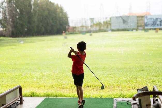 De jonge aziatische jongen oefent zijn golfschommeling bij de golf driving range uit. Premium Foto