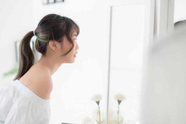 De jonge aziatische vrouw bekijkt spiegel Premium Foto