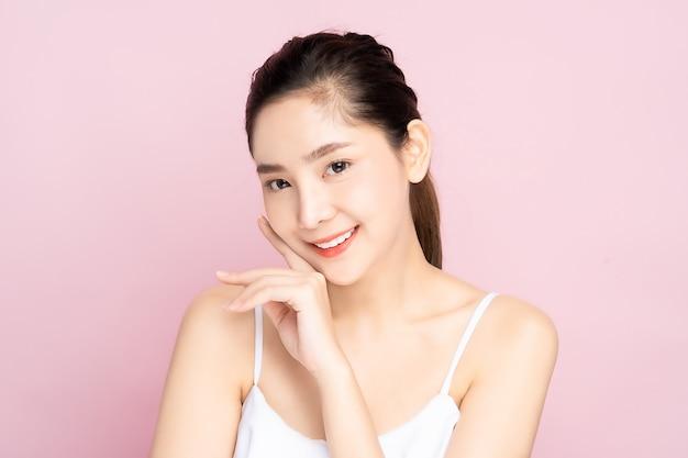 De jonge aziatische vrouw met schone verse witte huid wat betreft haar eigen gezicht zacht in schoonheid stelt Premium Foto