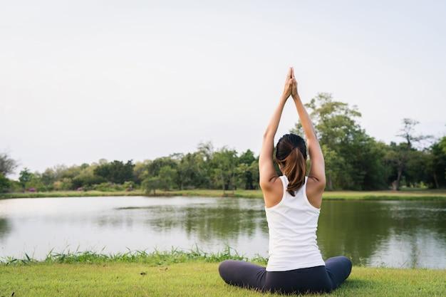 De jonge aziatische vrouwenyoga houdt in openlucht kalm en mediteert terwijl het praktizeren van yoga Gratis Foto