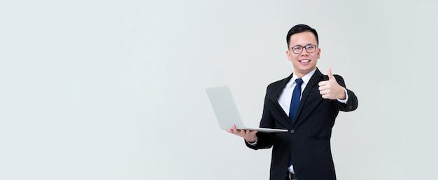 De jonge aziatische zakenman die met zijn online bedrijfs dragende laptop en het geven zijn beduimelt omhoog Premium Foto