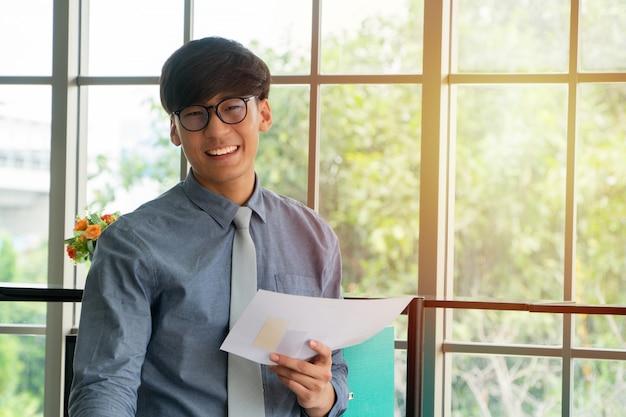 De jonge aziatische zakenman wekte gelukkig en het vieren succes op de werkplaats op Premium Foto