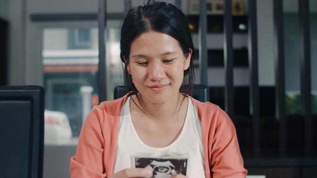 De jonge aziatische zwangere vrouwen tonen en kijkend de baby van de ultrasone klankfoto in buik. mamma die het gelukkige vreedzame glimlachen voelen terwijl thuis de zitting van het zorgkind op lijst in woonkamer thuis nemen. Gratis Foto