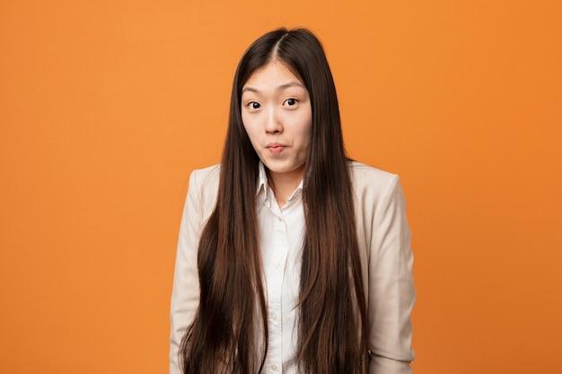 De jonge bedrijfs chinese vrouw haalt schouders op en verwarde ogen. Premium Foto