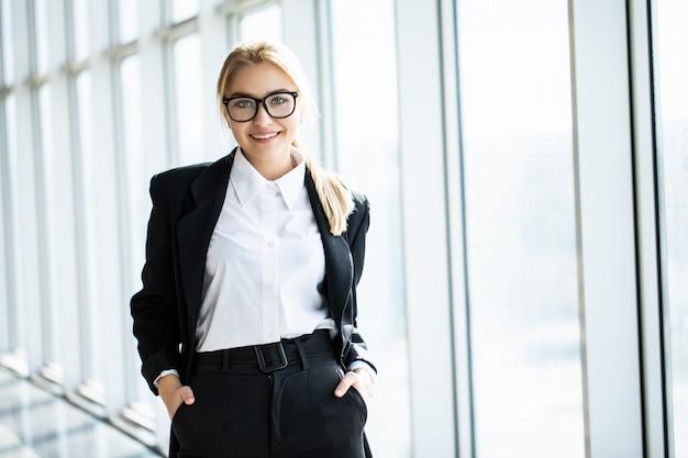 De jonge blondevrouw met gekruiste handen bevindt zich in het hoek panoramische bureau. Gratis Foto