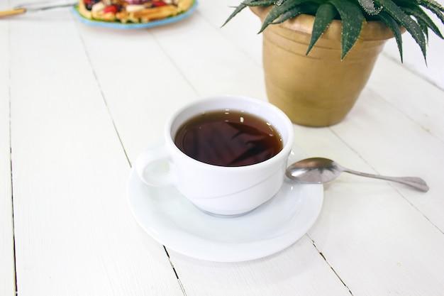 De jonge cafe die van de meisjeszitting ontbijtwafel met chocoladesaus, banaanplakken en aardbeien eten op groene ceramische plaat en fotografeerde haar ontbijt Gratis Foto
