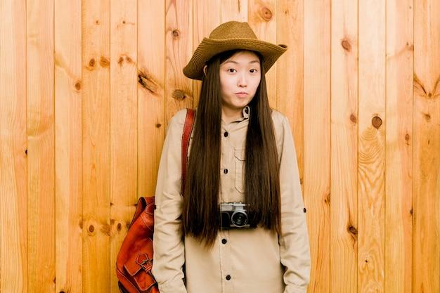 De jonge chinese reizigersvrouw haalt verwarde schouders en open ogen op. Premium Foto