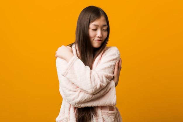 De jonge chinese vrouw in pyjama koestert zich, onbezorgd en gelukkig glimlachen. Premium Foto