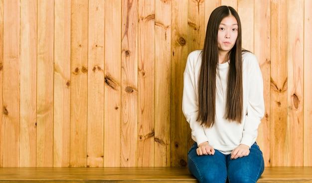 De jonge chinese vrouwenzitting op een houten plaats haalt schouders en open verwarde ogen op. Premium Foto