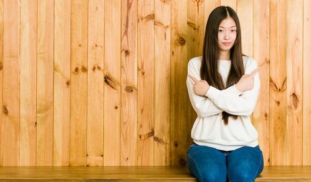 De jonge chinese vrouwenzitting op een houten plaats richt zijdelings, probeert tussen twee opties te kiezen. Premium Foto